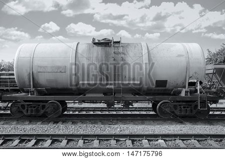 Cargo train with oil tanker. Wagon on station. Black and white photography