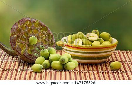 Fresh green lotus seed (lotus nut) in ceramic bowl and lotus seed box on green background