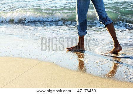 Adult man walking on he sea wave sand sunrice beach