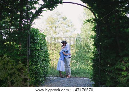 Man hugged the girl and kissed her on the forehead under the arch of the leaves