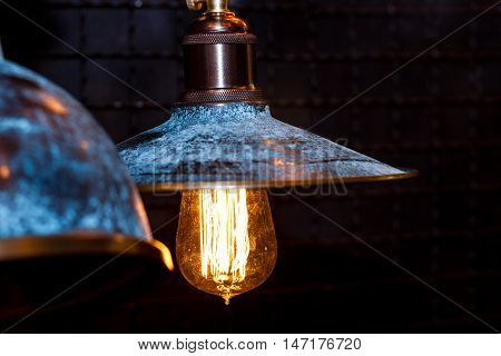 Old grunge blue lamp with wide lampshade and gleaming glass bulb