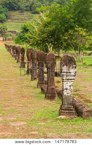 Selective focus of stone carved poles columns along walking path at Vat Phou, Wat Phu, Khmer Hindu temple complex and UNESCO World Heritage Site in Champasak Province, southern Laos