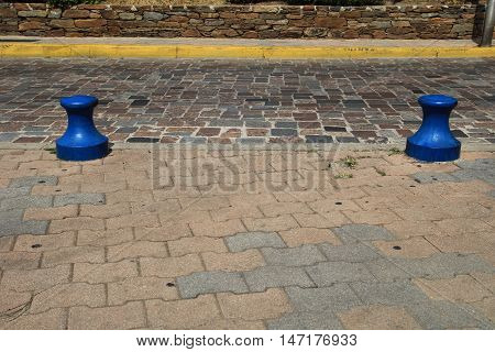 Two Blue Bollards On A Cobbled Street With Yellow No Parking Line In Background