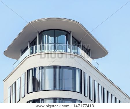 Abstract view of modern curver corner facade with rooftop terrace and canopy