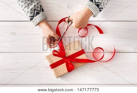 Woman is wrapping christmas or other holiday handmade present in paper with red ribbon. Making bow at present box, decoration of gift. Hands on white wooden table, top view.