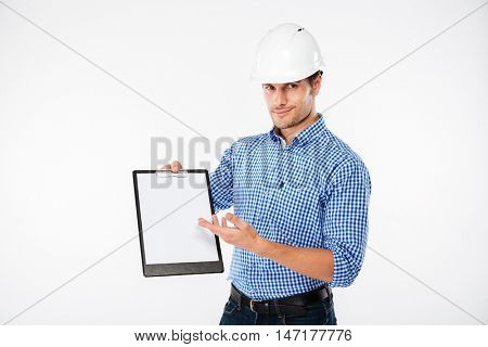 Happy young man building engineer in hard hat holding and pointing on blank clipboard