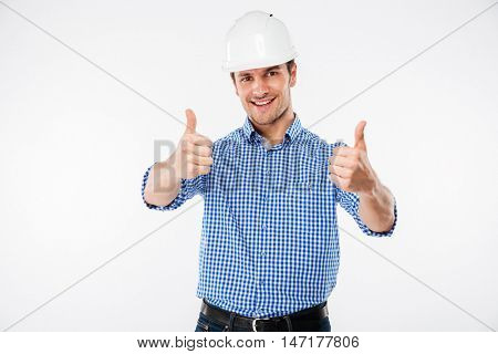 Cheerful young man engeneer in building helmet showing thumbs up with both hands over white background