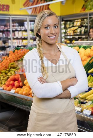 Saleswoman Standing Arms Crossed By Fruit Crates