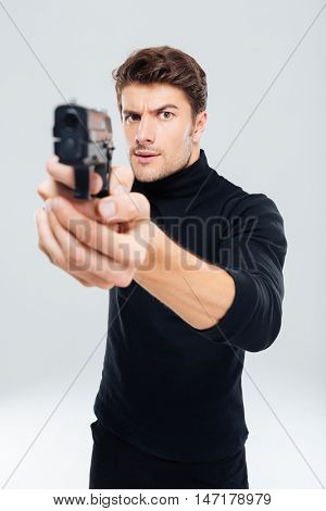 Concentrated young man standing and pointing with gun on you