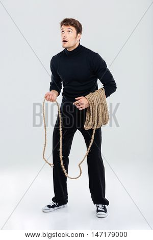 Full length of amazed young man with rope standing and looking up