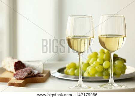 Glasses with white wine and grape on a table