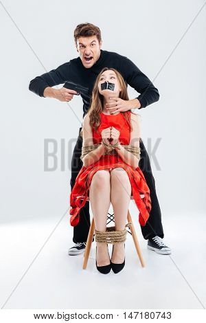 Furious angry man threatening scared woman by gun isolated on the white background