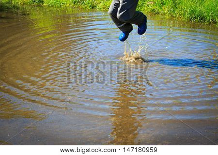 little boy in rain boots jumping into water puddle, kids seasonal activities