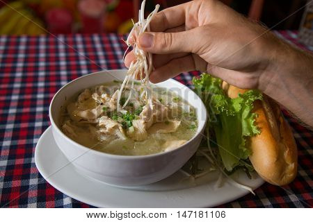 Vietnamese pho soup and a baguette in a cafe hands