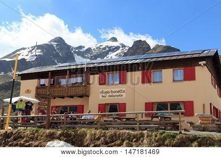 Valfurva, Italy - June 2, 2016: Alpine hut Rifugio Bonetta at gavia pass and mountain Monte Gavia. The gavia pass is one of the highets mountain passes in the Alps.