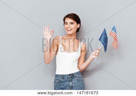 Patriotic happy woman holding european and usa flags and showing okay gesture over gray background