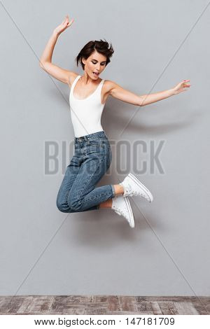 Laughing young brunette girl jumping over gray background