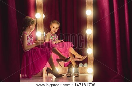 Cute little fashionista. Happy child girl try on outfits and mom's shoes looking at mirror.