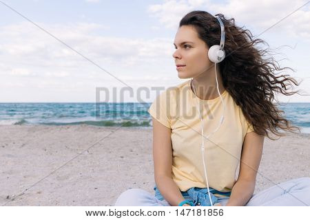 Girl with thick brown hair listening to music with headphones on the beach copy space