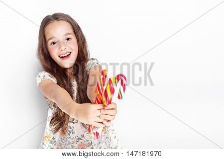 Happy, smiling cute little girl eating cristmas candy cane, posing against a white wall.