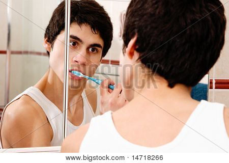 Reflection in a bathroom mirror of a young man brushing his teeth