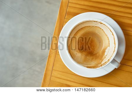 Coffee stain in a coffee cup on wood tabletop view angle.