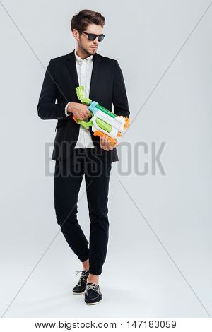 Attractive young handsome businessman in suglasses and suit holding water gun over gray background
