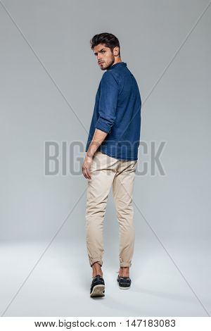 Back view portrait of a casual man walking and looking over shoulder over gray background