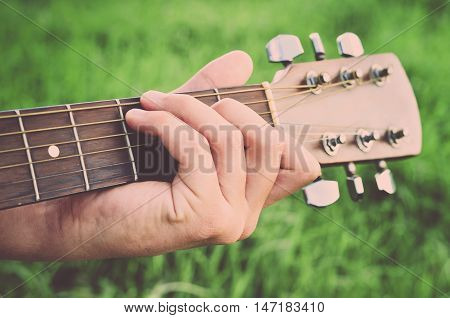 Man's hand and guitar close up (vintage)