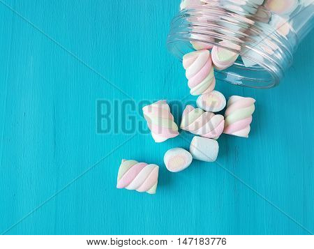 marshmallow candies in a jar on a turquoise background