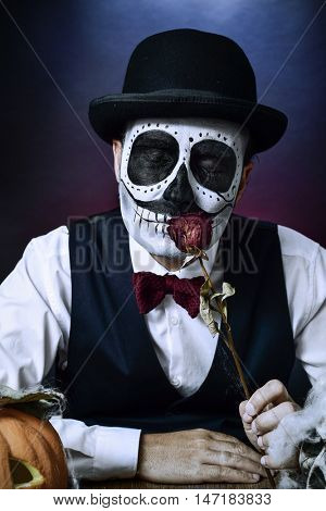 a man with a mexican calaveras makeup, wearing vest, bow tie and bowler hat, smells a dried rose, with a carved pumpkin and a skull in the foreground