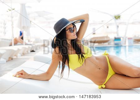 Portrait of a pretty young woman lying on deckchair outdoors at the swimming pool