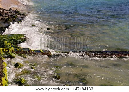 Waves crashing into rocky shoreline with sea grass growing on rocks with line of rocks heading out to sea