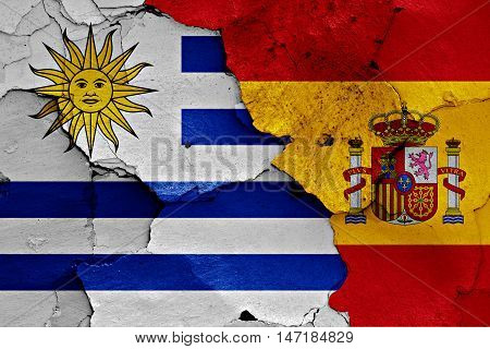 flags of Uruguay and Spain painted on cracked wall