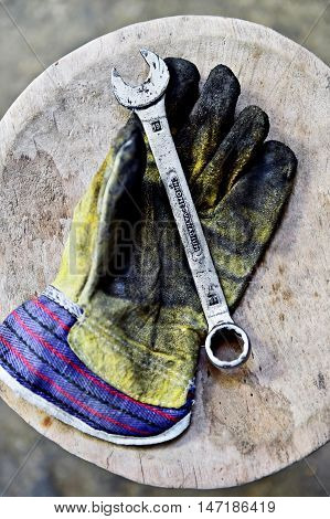 Dirty worker's glove holding a wrench key on a wooden plank in a workshop