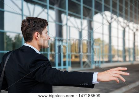 Young brunette businessman stopping car with hand outdoors