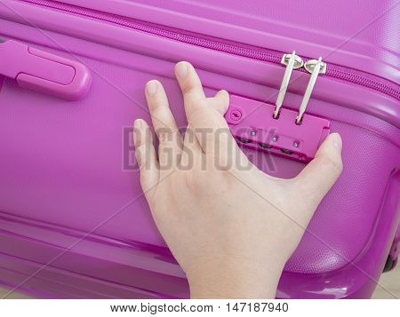 Woman use right hand to unlock zipper on pink suitcase