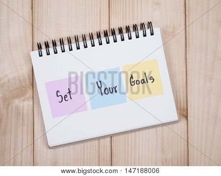 Handwriting Set Your Goals on notebook with wood background (Business Concept)