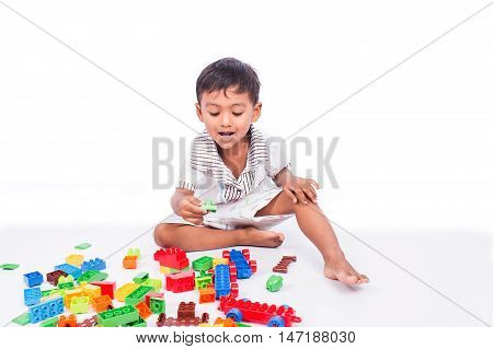 little asian boy play building brick on white background