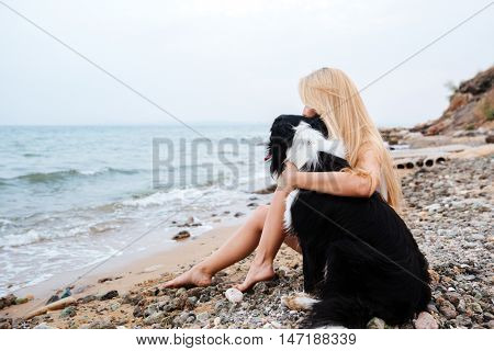 Blonde young woman sitting and hugging a dog on the beach