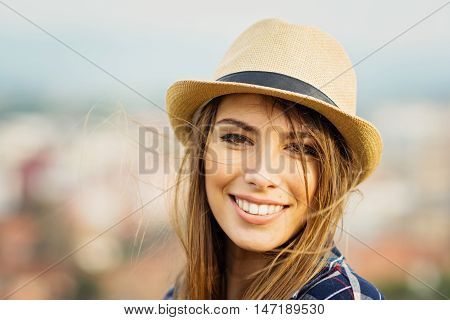 Closeup portrait of gorgeous blonde young woman in brown fedora on windy day. Gorgeous teenage girl with blonde hair, smiling, posing outdoors in autumn.