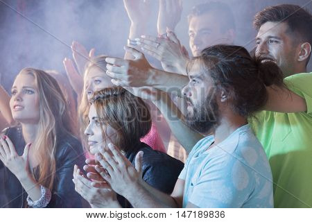 Shot of a group of young people clapping their hands at a concert