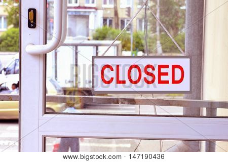 A sign with red letters on the front door