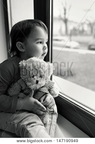 Little girl looking out the window at home