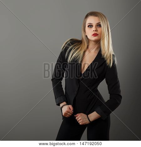 Business girl posing in the studio on a gray background
