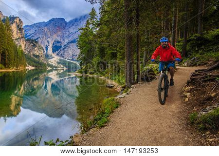 View of cyclist riding mountain bike on trail by the lake in Dolomites, Lago di Braies, Italy