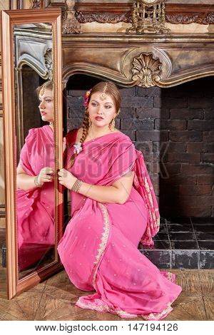 Woman in pink dress with decorations on head sits at fireplace holding large mirror in room.