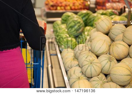 Woman Shopping For Groceries In Supermarket Standing With Her Back