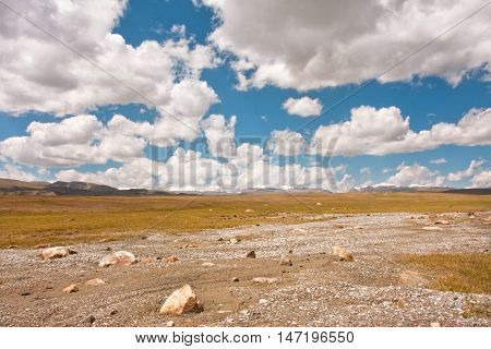 Poor road on a plateau under the big white clouds Central Asia