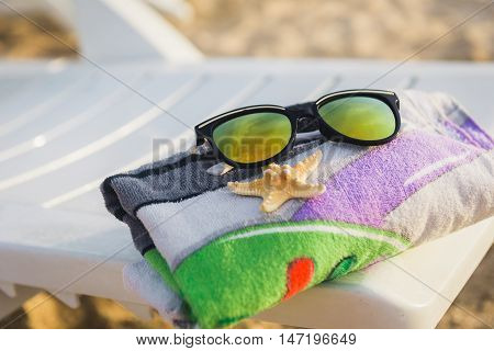 towel  starfish on a white plastic chaise-longue in the beach near the sea